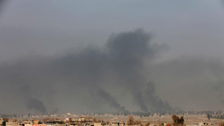 Smoke rises after an airstrike by U.S.-led coalition warplanes during fighting on the western side of Mosul, Iraq, Monday, Feb. 27. 2017. A senior Iraqi police commander said Monday that troops have taken control of the western side of a key bridge in Mosul amid intense clashes with the Islamic State group. The commander of the Federal Police Rapid Response Force, said his forces pushed into Mosul's western Gawsaq neighborhood Monday, reaching the foot of what's known locally as the 4th Bridge. (AP Photo/Khalid Mohammed)