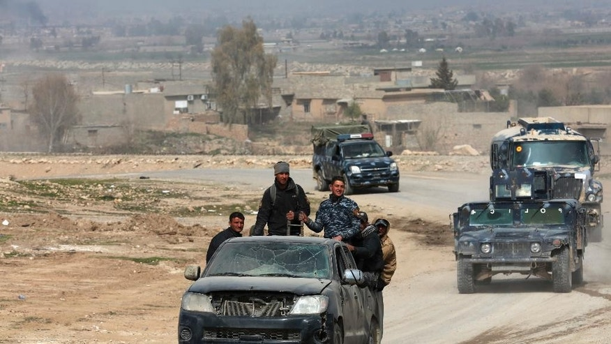 Iraqi forces advance during fighting against Islamic State militants on the western side of Mosul, Iraq, Monday, Feb. 27. 2017. A senior Iraqi police commander said Monday that troops have taken control of the western side of a key bridge in Mosul amid intense clashes with the Islamic State group. The commander of the Federal Police Rapid Response Force, said his forces pushed into Mosul's western Gawsaq neighborhood Monday, reaching the foot of what's known locally as the 4th Bridge. (AP Photo/Khalid Mohammed)