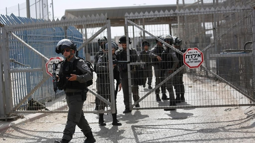 "Israeli border police deploy at the Israeli Qalandia checkpoint near Jerusalem, Monday, Feb. 27, 2017. Israeli police say an investigation is underway after forces at the checkpoint shot and wounded a Palestinian woman thinking she was planning an attack but later found she was unarmed. Spokeswoman said the woman entered a vehicle-only lane Monday and advanced toward officers holding ""something"" and was shot after ignoring calls to stop. (AP Photo/Majdi Mohammed) ??"