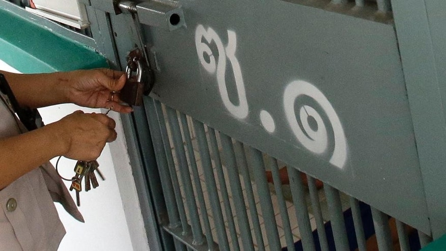 In this Jan. 6, 2017 photo, an officer locks a cell at a prison in Thailand. Thailand's prisons fail to meet international standards, with inmates routinely shackled, stuffed into overcrowded cells and forced to work in harsh conditions, an international human rights group said Tuesday, Feb. 28, 2017. (AP Photo/Sakchai Lalit)