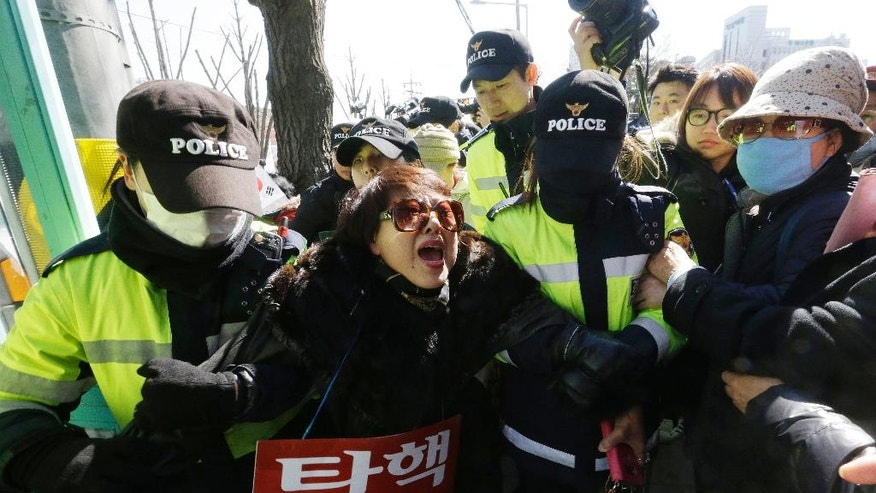 "A supporter of impeached South Korean President Park Geun-hye is detained by police officers during a rally opposing her impeachment as the Constitutional Court holds its final hearing in the impeachment trial of Park in front of the court in Seoul in Seoul, South Korea, Monday, Feb. 27, 2017. A special investigation team is wrapping up its probe into a huge scandal involving Park after the country's acting leader refused to extend its investigation past a Tuesday deadline. The sign read: ""Nullity of impeachment."" (AP Photo/Ahn Young-joon)"