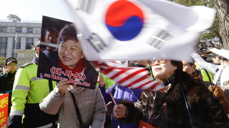 A supporter of impeached South Korean President Park Geun-hye waves flags of the U.S. and South Korea while another holds a portrait of the president during a rally opposing her impeachment as the Constitutional Court holds its final hearing in the impeachment trial of her outside the court in Seoul, South Korea, Monday, Feb. 27, 2017. A special investigation team is wrapping up its probe into a huge scandal involving Park after the country's acting leader refused to extend its investigation past a Tuesday deadline. (AP Photo/Ahn Young-joon)