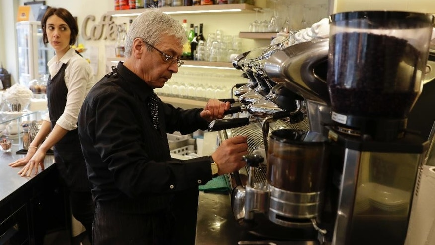 In this image taken on Monday, Feb. 27, 2017, waiter Ciro Chierchia prepares a traditional espresso coffe at a coffee bar in Milan, Italy. Longtime CEO Howard Schultz's vision for Starbucks was largely inspired by the Milan coffee bars he experienced on his first trip to the northern Italian city in 1983. Schultz will continue on with the company to open ''the quintessential Roastery'' in Milan by the end of 2018. (AP Photo/Luca Bruno)