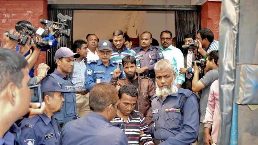 Bangladeshi policemen escort defendants, center, belonging to the militant group, Jumatul Mujahedeen Bangladesh, as they are brought to a court in Rangpur, Bangladesh, Tuesday, Feb. 28, 2017. Five members of the banned militant group were sentenced to death by the Bangladesh court Tuesday for their involvement in the slaying of a Japanese agricultural researcher two years ago. (AP Photo)