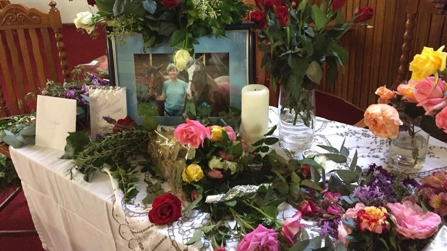 A table is set with flowers at a memorial service for murdered Sue Howarth, in photo, in Dullstroom, South Africa, Tuesday, Feb. 28, 2017. The service was held for Howarth, a British woman who was brutally assaulted and killed by attackers at her farm. Susan Howarth died on Feb. 21, two days after the attack. Her British husband, Robert Lynn, survived and has said he was burned with a blowtorch and slashed with a knife by assailants demanding money. Three suspects are being held without bail. (AP Photo)