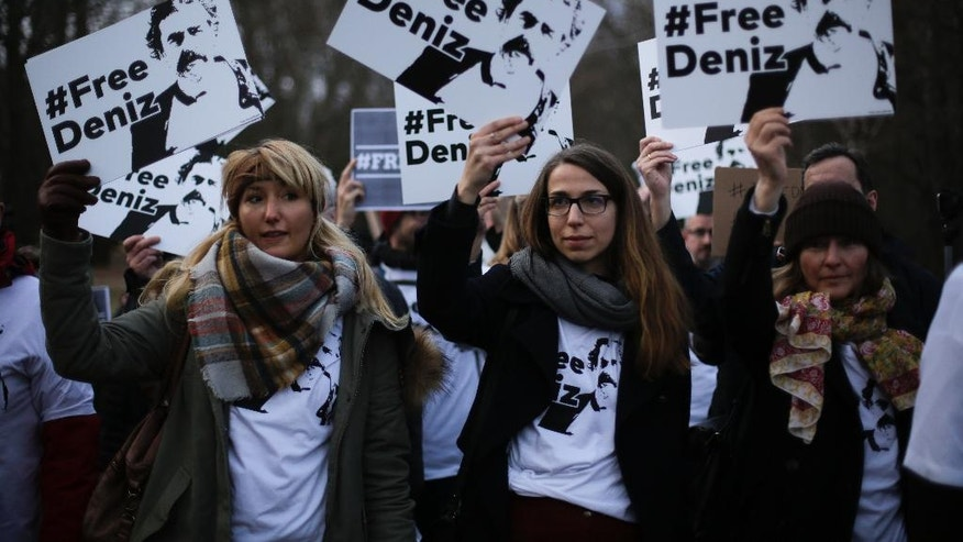Demonstrators hold posters and wear shirts with the slogan '#FREEDENIZ' during a protest in front of the Turkish embassy in Berlin, Tuesday, Feb. 28, 2017. The demonstrators protest against the police custody of Deniz Yucel, a correspondent in Turkey for the German daily newspaper 'Welt'. (AP Photo/Markus Schreiber)