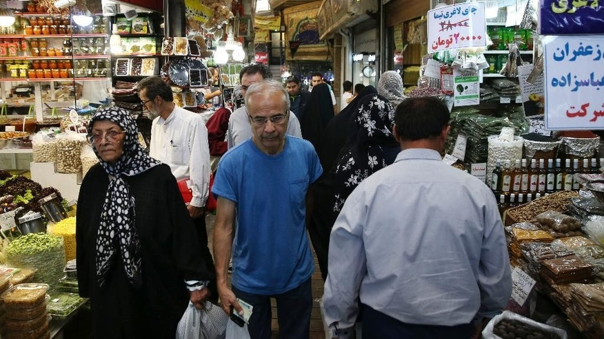 --FILE-- In this Tuesday, July 19, 2016, file photo, Iranians walk through Tajrish bazaar in northern Tehran, Iran. Iran's economy rebounded out of a recession after the nuclear deal with world powers, the International Monetary Fund said on Tuesday, though uncertainty over future sanctions and problems plaguing the country's domestic banks could cause fiscal trouble ahead. (AP Photo/Vahid Salemi, file)