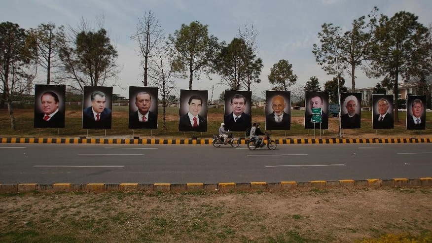 Motorcyclists drive past billboards showing heads of state, from left to right, of Pakistan, Tajikistan, Turkey, Turkmenistan, Uzbekistan, Afghanistan Azerbaijan, Iran, Kazakhstan and Kyrgyzstan on a main highway to welcome them in Islamabad, Pakistan, Tuesday, Feb. 28, 2017. Pakistan will host representatives from 10 countries of the Economic Cooperation Organization on Wednesday to finalize a plan for expanding trade and prosperity in the region. (AP Photo/Anjum Naveed)