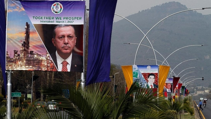 Billboards showing portraits of presidents of Turkey, Turkmenistan and Kyrgyzstan are displayed at a main highway to welcome them in Islamabad, Pakistan, Tuesday, Feb. 28, 2017. Pakistan will host representatives from 10 countries of the Economic Cooperation Organization on Wednesday to finalize a plan for expanding trade and prosperity in the region. (AP Photo/Anjum Naveed)