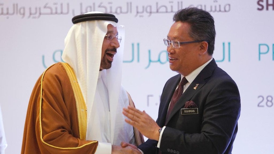 Saudi's Energy Minister Khalid Al-Falih, left, shakes hands with Malaysia's Minister in the Prime Minister's Department Abdul Rahman Dahlan during a press conference at a hotel in Kuala Lumpur, Malaysia, Tuesday, Feb. 28, 2017. Saudi Arabia and Malaysia signed four major agreements Monday that will go a long way in cementing ties between the two countries. (AP Photo/Daniel Chan)