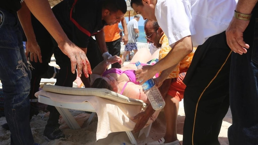 "FILE - This is a Friday, June 26, 2015 file photo of an injured person being  treated on a Tunisian beach, in Sousse Tunisia. A British coroner said the Tunisian police response to a deadly gun attack on the beach resort of Sousse was ""at best shambolic, at worst cowardly."" Judge Nicholas Lorraine-Smith is delivering his findings Tuesday Feb. 28, 2017 at an inquest into the deaths of 30 British tourists killed in the June 2015 attack at the five-star Riu Imperial Marhaba hotel. (Jawhare FM/File via AP)"