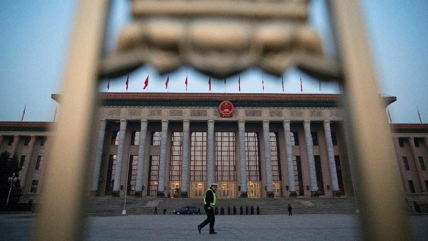 FILE - In this March 5, 2015 file photo, a Chinese traffic policeman walks in front of the Great Hall of the People before the opening session of the National People's Congress in Beijing. Democracy Chinese-style will go on display when the country's rubberstamp legislature, the National People's Congress opens its annual sessions in Beijing on Sunday, March 5, 2017. (AP Photo/Ng Han Guan, File)