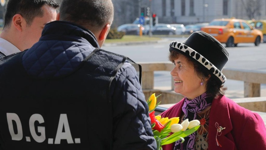 "A woman smiles after receiving flowers and a spring charm from Romanian anti-corruption officers in Bucharest, Romania, Wednesday, March 1, 2017. Officers from a government anti-corruption unit DGA handed out flowers and ""martisori"" (the word comes from the Romanian for March) with an anti-graft message to women in the Romanian capital.(AP Photo/Vadim Ghirda)"