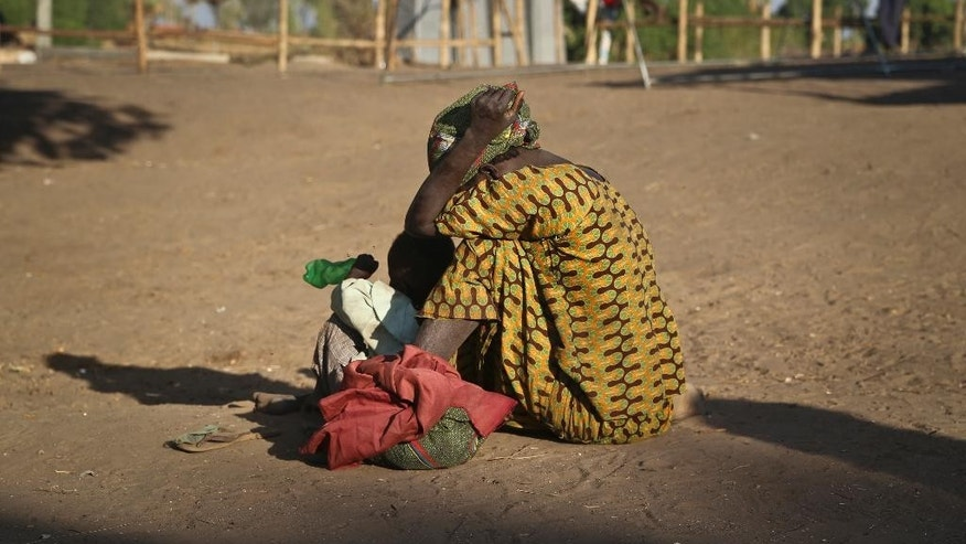 In this photo taken Thursday, Feb. 16, 2017, a South Sudanese refugee woman sits with her child at a refugee collection center in Palorinya, Uganda. More than 100,000 people have fled a single county in South Sudan in just three months as civil war continues amid warnings of genocide, and the surge of more than half a million South Sudanese refugees into Uganda since July has created Africa's largest refugee crisis. (AP Photo/Justin Lynch)