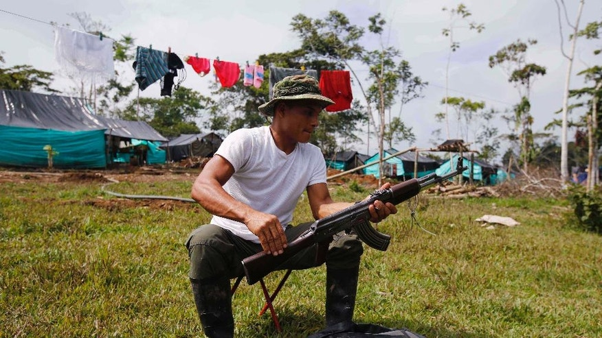 Revolutionary Armed Forces of Colombia, FARC, rebel cleans his weapon at a camp in La Carmelita near Puerto Asis in Colombia's southwestern state of Putumayo, Tuesday, Feb. 28, 2017. March 1 was the deadline for the FARC to turn over 30 percent of their arms. But logistical delays setting up the rural camps where rebels are gathered has slowed the process. (AP Photo/Fernando Vergara)