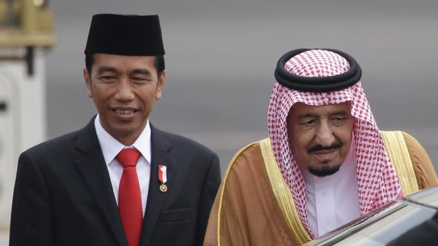 Saudi King Salman, right, walks with Indonesian President Joko Widodo upon arrival at Halim Perdanakusuma Airport in Jakarta, Indonesia, Wednesday, March 1, 2017. Salman arrived in the world's largest Muslim nation on Wednesday as part of a multi-nation tour aimed at boosting economic ties with Asia. (AP Photo/Dita Alangkara)