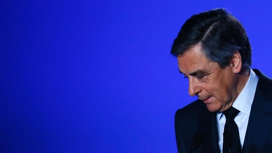 Conservative presidential candidate Francois Fillon leaves after delivering his speech at his campaign headquarters in Paris, Wednesday, March 1, 2017. Fillon is refusing to quit the race despite receiving a summons Wednesday to face charges for alleged fake parliamentary jobs for his family. (AP Photo/Francois Mori)
