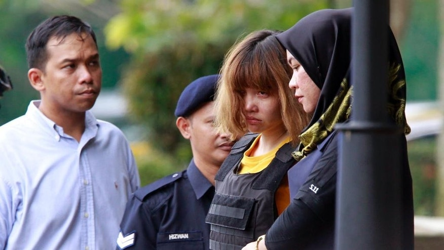 Vietnamese suspect Doan Thi Huong, second from right, in the ongoing assassination investigation, is escorted by police officers out from Sepang court in Sepang, Malaysia on Wednesday, March 1, 2017. Appearing calm and solemn, two young women accused of smearing VX nerve agent on Kim Jong Nam, the estranged half brother of North Korea's leader, were charged with murder Wednesday. (AP Photo/Daniel Chan)