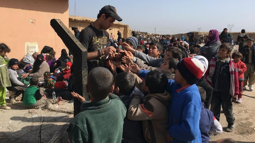 An Iraqi Army soldier distributes candies to displaced children as they flee their homes due to fighting between Iraqi security forces and Islamic State militants, on the western side of Mosul, Iraq, Tuesday, Feb. 28. 2017. Since Iraqi government forces launched the push to take the western half of Mosul from the Islamic State group last week, about 8,000 people have fled from that part of the city and surrounding villages, the U.N. humanitarian aid agency said Tuesday. (AP Photo/Mohammed Saad)