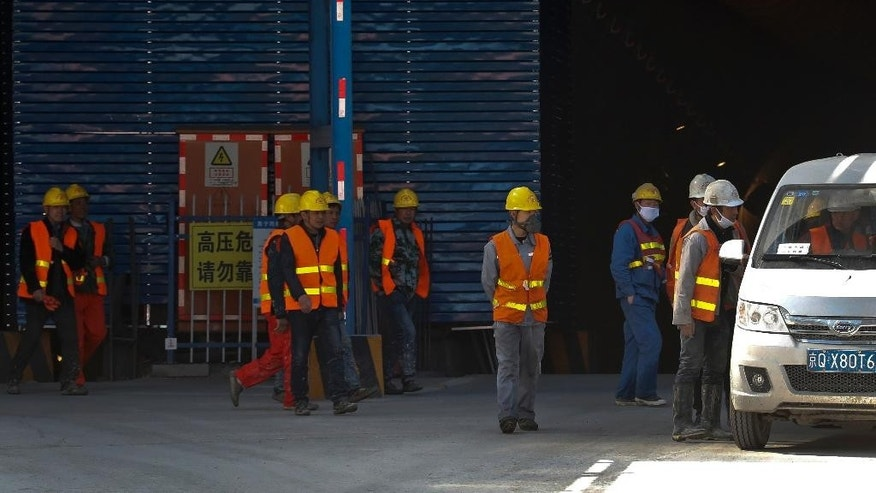 Chinese workers leave for their lunch break at the construction site of the Badaling Great Wall Station in between of Beijing-Zhangjiakou high-speed railway, in Beijing, Wednesday, March 1, 2017. China's Labor Minister Yin Weimin said Beijing will cut another 500,000 jobs this year from steel, coal and other heavy industries to reduce excess production capacity that is flooding markets and depressing global prices. (AP Photo/Andy Wong)