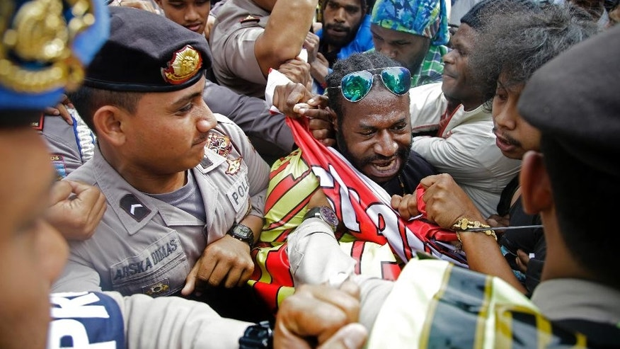 FILE - In this Thursday, Dec. 1, 2016, file photo, West Papuan protesters scuffle with the police during a rally calling for the remote region's independence, in Jakarta, Indonesia. Seven Pacific island nations have called for a U.N. investigation into allegations of human rights abuses in Indonesia's West Papua and Papua provinces, where a separatist movement has simmered for decades. (AP Photo/Dita Alangkara, File)