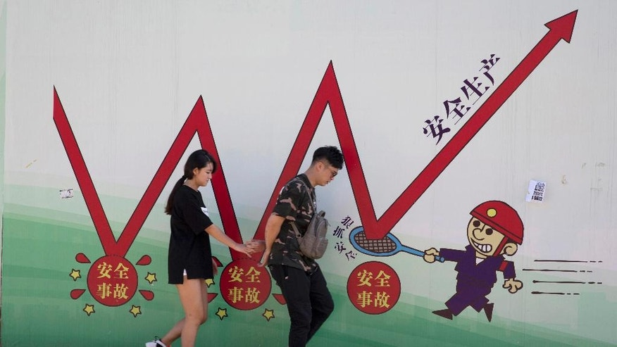 "FILE - In this Aug. 25, 2016 file photo, a couple walks in front of a work safety propaganda billboard in Beijing, China. Instead of dramatic new reforms, Chinese leaders are likely to emphasize reining in surging debt and financial risks to keep growth steady at this year's meeting of the ceremonial national legislature. Chinese character at right reads ""Safe Production."" (AP Photo/Ng Han Guan, File)"