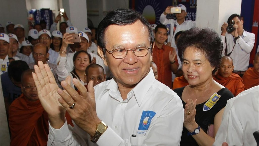 Opposition party Cambodia National Rescue Party (CNRP) President Kem Sokha, foreground, claps to party supporters during the party's political congress in Phnom Penh, Cambodia, Thursday, March 2, 2017. Prominent politician Kem Sokha has been selected Thursday as the country's new leader of main opposition party to challenging the upcoming elections with his arch rival, long-serving Prime Minister Hun Sen. (AP Photo/Heng Sinith)