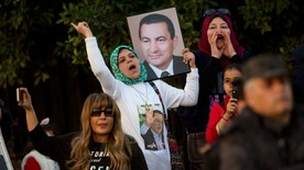 A small number of supporters of ousted former Egyptian President Hosni Mubarak hold posters with his photo, as they celebrate outside Maadi Military Hospital, where he is hospitalized, in Cairo, Egypt, Thursday, March 2, 2017. Egypt's top appeals court found Mubarak innocent of complicity in the killings of protesters during 2011 Egyptian uprising. (AP Photo/Amr Nabil)