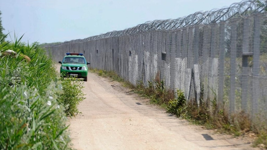 FILE - In this July 5, 2016 file photo a Hungarian police vehicle patrols by the border fence between Hungary and Serbia near Asotthalom, Hungary. Hungary has begun building a second fence on its border with Serbia meant to stop migrants and refugees from freely entering the country as a government spokesman confirmed Monday, Feb. 27, 2017. (Edvard Molnar/MTI via AP, file)