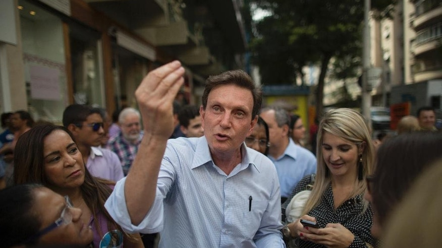 FILE - In this Sept. 29, 2014 file photo, retired Pentecostal Bishop Marcelo Crivella campaigns for the governorship of Rio de Janeiro state, in Brazil's Copacabana. During Rio's world famous Carnival bash, Crivella, elected mayor of Rio in Oct. 30, 2016, made a decision unheard of in modern times for city leaders during its most important event: he completely skipped the bash, even standing up members of a ceremonial group on opening night. (AP Photo/Leo Correa, File)