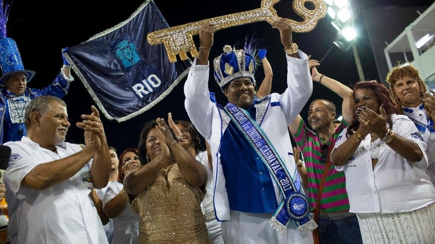 FILE - In this Feb.24, 2017 file photo, Carnival King Momo, Fabio Damiao dos Santos Antunes, holds up the key to the city at a ceremony marking the official start of Carnival in Rio de Janeiro, Brazil. Rio Mayor Marcelo Crivella, a retired Pentecostal Bishop stood up the group that traditionally participates in the ceremony where he hands a symbolic key of the city to King Momo, or the king of carnal delights. (AP Photo/Mauro Pimentel, File)