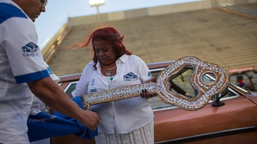 FILE - In this Feb.24, 2017 file photo, Maria Cristina de Jesus, the guardian of Rio's city key, places the oversized key in a bag during a delay in the officially kick off Carnival ceremony, at the Sambadrome in Rio de Janeiro, Brazil.  After spending all day waiting for Rio de Janeiro Mayor Marcelo Crivella to show up for the ceremony, the head of Rio's tourism agency came instead, and apologized saying that Mayor Crivella's wife was sick. (AP Photo/Mauro Pimentel, File)