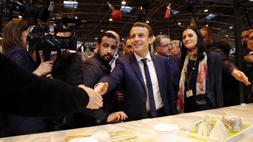 Centrist presidential candidate Emmanuel Macron, center, shakes hands with a farmer at a cheeses stand as he visits the Agriculture Fair in Paris, Wednesday, March 1, 2017. The first French presidential ballot will take place on April 23 and the two top candidates go into a runoff on May 7. (AP Photo/Christophe Ena)