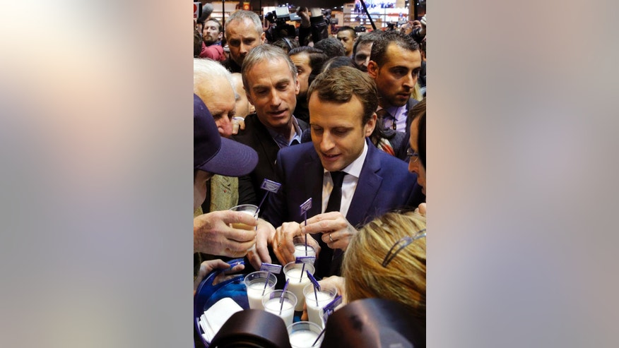 Centrist presidential candidate Emmanuel Macron tastes milk as he visits the Agriculture Fair in Paris, Wednesday, March 1, 2017. The first French presidential ballot will take place on April 23 and the two top candidates go into a runoff on May 7. (AP Photo/Christophe Ena)