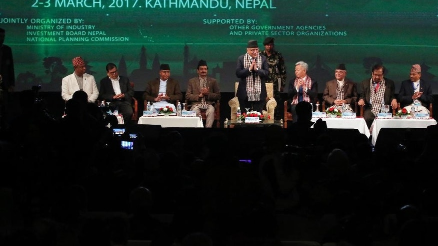 Nepalese Prime Minister Pushpa Kamal Dahal, center, greets the audience as Asian Infrastructure Investment Bank President Jin Liqun, fourth right, and others attend the Nepal Investment Summit in Kathmandu, Nepal, Thursday, March 2, 2017. Nepal has gathered investors from some 30 countries hoping to reel in foreign investment for development of the nation still recovering from devastating earthquake and struggling with political instability. (AP Photo/Niranjan Shrestha)
