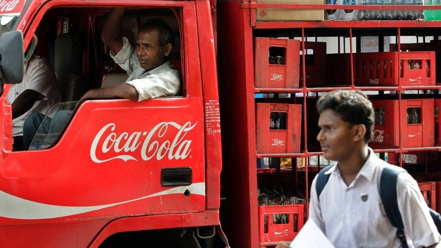 FILE - In this June 26, 2012 file photo, a man walks past a truck that distributes Coca Cola in Mumbai, India. Traders have pulled Coke and Pepsi off their store shelves in south India in anger at PETA's opposition to a local bull-taming sport. The Tamil Nadu Traders Association said the soft-drink makers were draining too much of the state's water but that they targeted the iconic American brands because the U.S. animal rights group pushed for a ban on the popular local tradition of Jallikattu. (AP Photo/Rajanish Kakade, File)