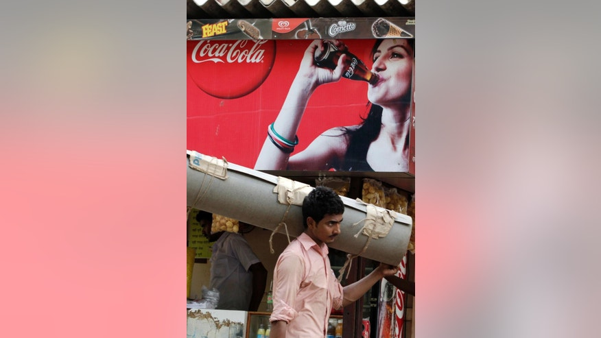 FILE- In this June 26, 2012 file photo, a man carries goods past a Coca Cola advertisement displayed at a food stall in Mumbai, India.  Traders have pulled Coke and Pepsi off their store shelves in south India in anger at PETA's opposition to a local bull-taming sport. The Tamil Nadu Traders Association said the soft-drink makers were draining too much of the state's water but that they targeted the iconic American brands because the U.S. animal rights group pushed for a ban on the popular local tradition of Jallikattu. (AP Photo/ Rajanish Kakadu, File)