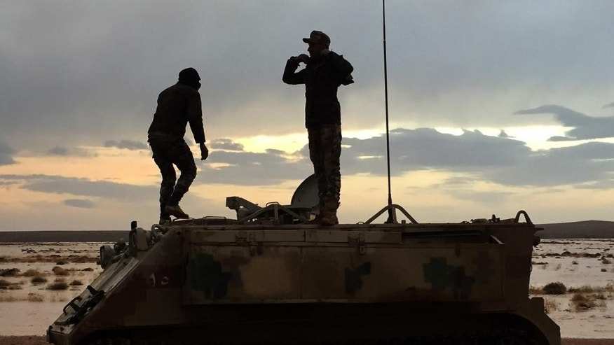 In this Wednesday, March 1, 2017 photo, two Jordanian soldiers take a break on their armored vehicle while escorting a U.N. aid convoy in the remote desert along the Jordan-Syria border. U.N. agencies have ramped up aid deliveries to tens of thousands of war-displaced Syrians stranded in the border area, after months of being denied access, but harsh weather and security problems frequently disrupt one of the U.N.'s most complex aid missions anywhere. (AP Photo/Karin Laub)