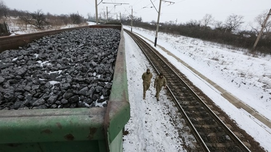 Activists walk along carriages loaded with coal from the occupied territories which they blocked at Kryvyi Torets station in the village of Shcherbivka in Donetsk region, Ukraine, February 14, 2017.