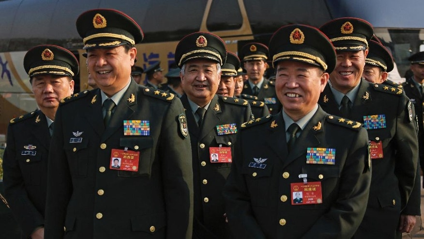 Delegates from China's People's Liberation Army (PLA) share a light moment as they arrive to attend a plenary session of the National People's Congress at the Great Hall of the People in Beijing, Saturday, March 4, 2017. China will raise its defense budget by about 7 percent this year, a government spokeswoman said Saturday, continuing a trend of lowered growth amid a slowing economy. (AP Photo/Andy Wong)