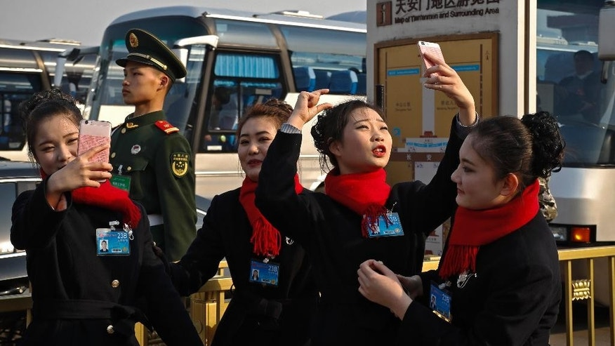 Bus ushers try to take selfies with a Chinese paramilitary policeman stands on duty during the Chinese People's Political Consultative Conference (CPPCC) at the Great Hall of the People in Beijing, Friday, March 3, 2017. Thousands of delegates have gathered at the Chinese capital for the opening of the annual session of the Chinese People's Political Consultative Conference, which advises the rubberstamp parliament, whose annual session begins Sunday. (AP Photo/Andy Wong)