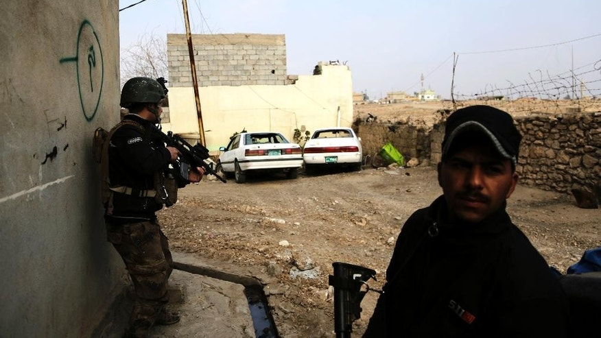Iraqi forces clear a street on the edge of Mosul's Mamun neighborhood on Friday, March 1, 2017. After launching an operation to retake Mosul's remaining Islamic State group held districts nearly two weeks ago, Iraqi forces continue to work to secure a belt of districts along the city's southwestern edge. (AP Photo/Susannah George)