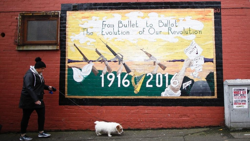 A woman walks her dog past a Republican mural in West Belfast, Northern Ireland, Thursday, March 2, 2017. Voting has begun Thursday in the British province of Northern Ireland to elect a new Stormont Assembly after the power-sharing government collapsed in January. (AP Photo/Peter Morrison)