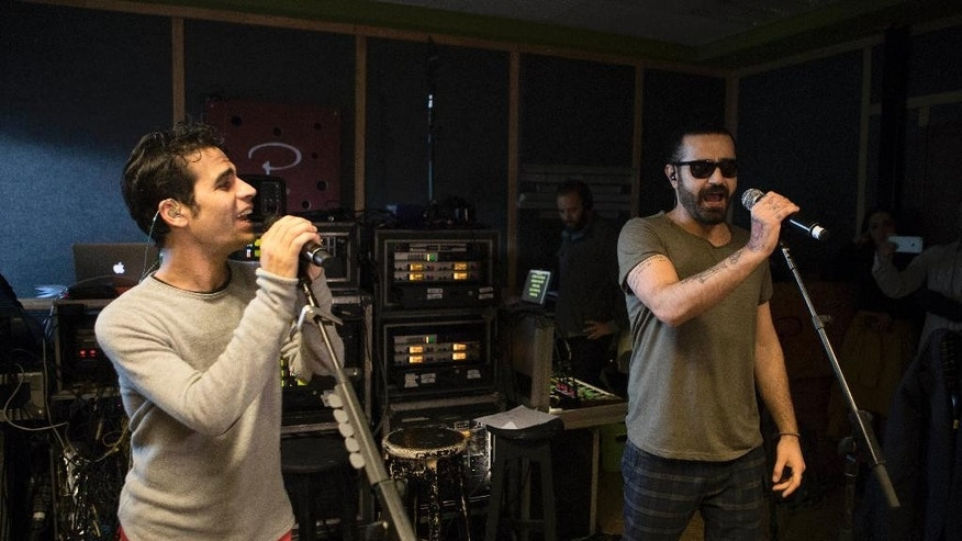 In this Monday, Feb. 27, 2017 photo, Iranian Shahin Najafi, right, and Israeli Aviv Geffen singers rehearse in Tel Aviv, Israel. In a first joint Israeli-Iranian concert, the rockers hope to prove that despite the bitter enmity between their countries the people can unite in the name of a better future. Geffen and Najafi say their Hebrew-Farsi fusion offers hope in a volatile region. (AP Photo/Dan Balilty)