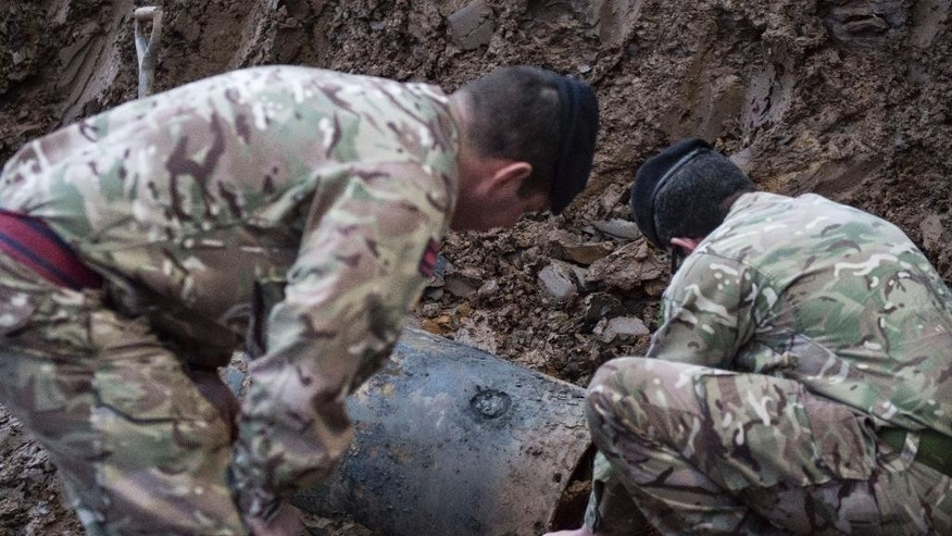 In this image taken Thursday March 2, 2017  released  by the Ministry of Defence shows  a Second World War bomb which was discovered on a building site in Brent, north-west London.  British Army bomb disposal team were  called in to dispose of a 500-pound World War II bomb found buried on a building site in northwest London. Schools, businesses and homes were evacuated and roads closed as experts from the Army's Royal Engineers  to make the German bomb safe. (Rupert Frere/MoD via AP)