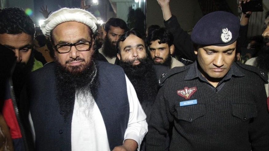 FILE - In this Monday, Jan. 30, 2017 file photo, a Pakistani police officer escorts Hafiz Saeed, left, Chief of Pakistan's religious group Jamaat-ud-Dawa outside party's headquarters in Lahore, Pakistan. Last month Pakistan placed Hafiz Saeed, a declared terrorist with a U.S. imposed $10 million bounty on his head, under house arrest, yet Sanaullah questioned allegations against Saeed, mostly connected to militant attacks in Indian held Kashmir, a Himalayan region, whose ownership is contested by both Pakistan and India and claimed by both in its entirety. (AP Photo/K.M. Chaudary, File)