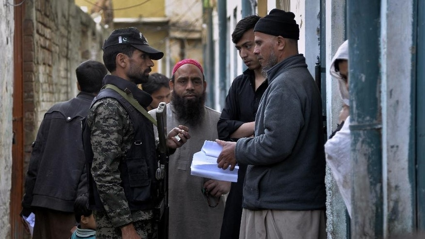 In this Thursday, Feb. 23, 2017 photo, a Pakistani paramilitary soldier checks documents of a resident during a search operation in the neighborhood of Rawalpindi, Pakistan. Rana Sanaullah, Punjab's provincial law minister said police were searching out areas in Punjab dominated by ethnic Pashtuns and unregistered Afghan refugees because some of the worst attacks carried out in the provincial capital of Lahore involved residents of the tribal areas. (AP Photo/Anjum Naveed)
