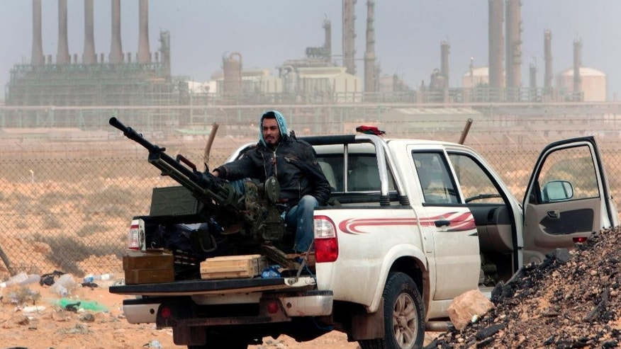 FILE - In this March 5, 2011 file photo, an anti-government rebel sits with an anti-aircraft weapon in front an oil refinery in Ras Lanouf, eastern Libya. Libyan armed forces based in the east have launched more airstrikes against militias that seized oil terminals a day earlier, saying forces from the country's rival west were declaring war against them. Col. Ahmed Mosmary, spokesman for forces commanded by army chief Gen. Khalifa Hifter, says three airstrikes have hit targets in the area around the al-Sidra and Ras Lanuf terminals, where at least nine soldiers were killed in Friday's attack that drove out the army. (AP Photo/Hussein Malla, File)