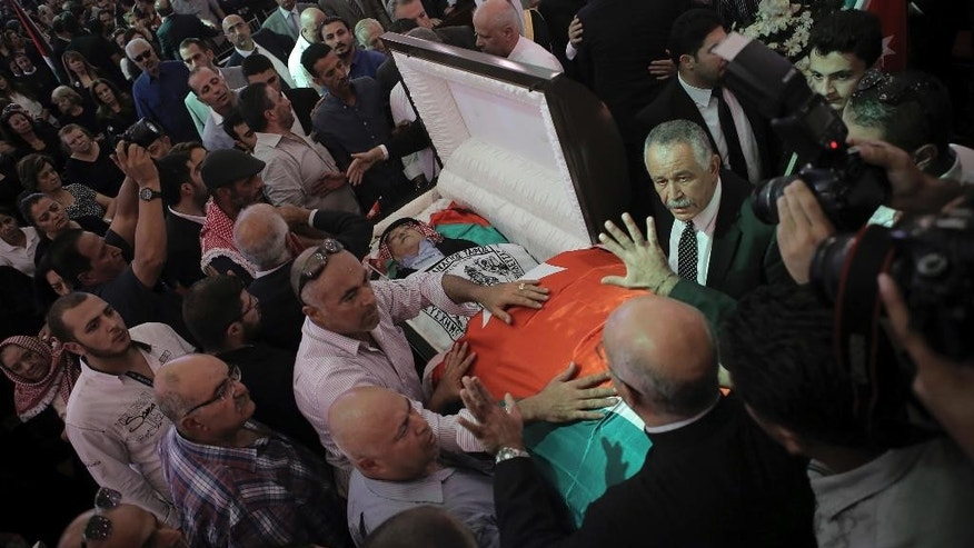 FILE - In this Wednesday, Sept. 28, 2016, file photo, relatives and activists of Jordanian writer Nahed Hattar, who was shot dead, takes a farewell look during his funeral in the town of Al-Fuheis near Amman, Jordan. Nahad Hattar, the writer, had been on trial for posting a cartoon deemed offensive to Islam on social media when an assailant killed him outside the courthouse. The shooter was a former mosque prayer leader motivated by anger over the cartoon, officials said at the time. (AP Photo/Raad Adayleh)