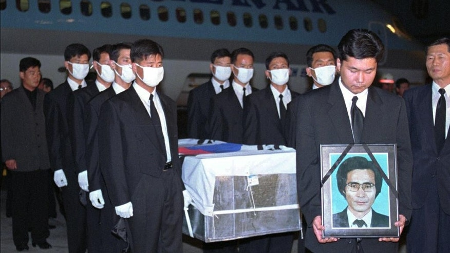 FILE - In this Oct. 5,1996 file photo, government officers carry a portrait and a coffin containing South Korean Choi Duk-kun, a South Korean diplomat stationed in the eastern Russian city of Vladivostok, upon the body's arrival at Gimpo International Airport in Seoul, South Korea. Choi was found dead in front of his apartment in 1996. He had head wounds, but his passport and money were still in his pockets. (AP Photo/Yun Jai-hyoung, File)